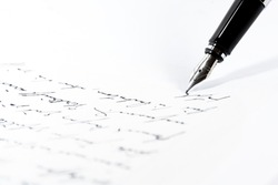 Black fountain pen is writing a letter or a manuscript on a white paper, copy space, close-up shot with selected focus and narrow depth of field