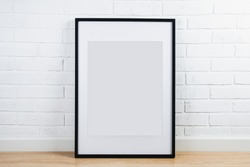 Black frame for painting or poster on white brick wall