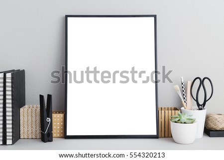 Black frame mock up on gray background, office supplies, stylish scissors, small plant. Arranagement inspiration.