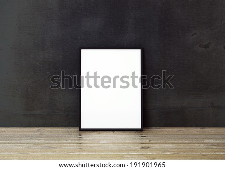 Black frame on wooden floor in black interior