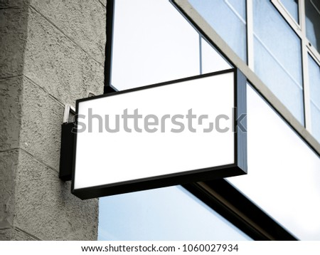 Black frame signboard side view of empty white mock-up modern with city brick wall background exterior display. Signboard side view of empty white mock up, squared, box, signage. #1060027934