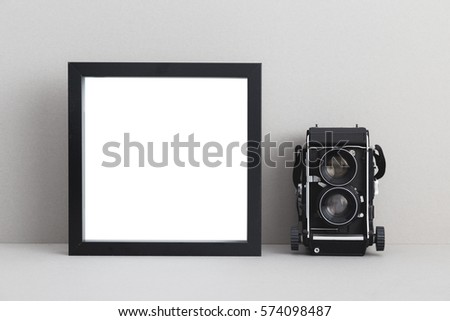 Black frame(square) and camera on shelf or desk.