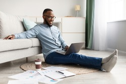 Black Freelancer Guy Working On Laptop Sitting On Floor Browsing Internet At Home. Freelance Career And Lifestyle, Distance Job Concept. African Man Using Computer Indoors