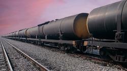 Black freight train wagons having oil tankers waiting on the rails againt sunrise sky