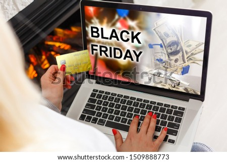 Black Friday advertisement in a laptop screen while woman buys by internet at home.