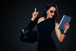 Black Friday and Cyber Monday sale concept for shop. Shopping woman holding bag and pointing on tablet isolated on dark background