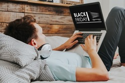 Black Friday banner in a laptop computer while man uses it to buy by internet lying down at home.