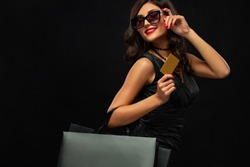 Black friday concept. Shopping woman holding bag and sale card isolated on dark background in holiday. Girl in sunglasses.