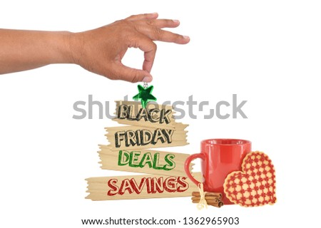 Black Friday Deals Savings Wood Tree Shape Sign Green Star hanging next to red mug heart shaped cookie and cinnamon sticks from hand white background #1362965903