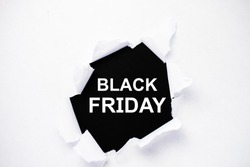 black Friday is written on a black background in the center of a torn white paper.