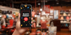 Black friday sale advert on mobile phone. The concept of shopping online. Shop with discounts in background