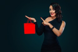 Black friday sale concept. Beautiful girl with red bag for shop on blackfriday. Happy young woman standing isolated over dark background pointing to looking left.