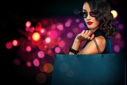 Black Friday sale concept for shop. Beautiful girl in sunglasses holding big bag isolated on background with lights at shopping on blackfriday.