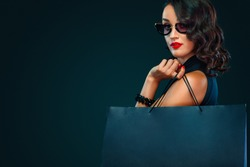 Black Friday sale concept for shop. Beautiful girl in sunglasses holding big bag isolated on dark background at shopping on blackfriday.