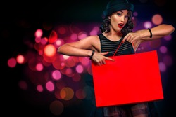 Black friday sale concept for shop. Female holding red bag isolated on background with lights at shopping on blackfriday. Woman pointing to looking on copy space.