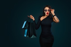 Black Friday sale concept for shop. Girl in sunglasses holding big bag isolated on dark background at shopping on blackfriday.