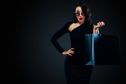 Black Friday sale concept for shop. Surprised woman in sunglasses holding bag isolated on dark background at shopping.