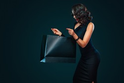 Black Friday sale concept for shop. Surprised woman in sunglasses holding bag isolated on dark background at shopping on blackfriday.