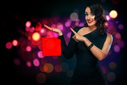 Black friday sale concept for shops. Girl holding red bag isolated on background with lights at shopping on blackfriday. Woman pointing to looking on copy space.
