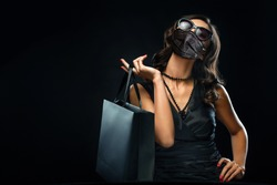 Black friday sale concept in 2020 - time of coronavirus pandemic. Shopping woman in medical mask holding grey bag isolated on dark background in holiday.