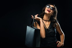Black friday sale concept. Shopping woman holding grey bag isolated on dark background in holiday