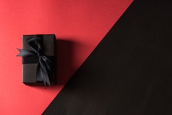Black Friday sale shopping concept, Top view of gift box wrapped in black paper and black bow ribbon, studio shot isolated on red and dark background