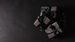 Black Friday sale shopping concept, Top view of gift box wrapped in black paper and black bow ribbon, studio shot on dark background