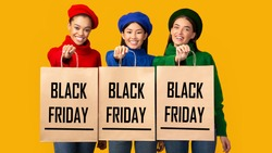 Black Friday Sales. Three Multiethnic Girls Holding Shopping Bags With Promo Text Standing Over Yellow Background. Panorama