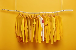 Black Friday, shopping and big sales concept. Detail image of yellow clothes and white sweater with label tag hanging on rack in clothing store. Shopping mall suggests customers season discounts