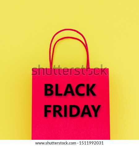 Black Friday text on red paper shopping bag and yellow wrapping paper background, close up.  Black Friday sale concept. Zero waste No Plastic
