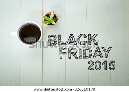 Black Friday 2015 text with a cup of coffee on pastel green wooden table #326810198