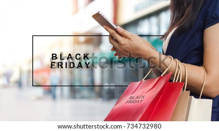 Black Friday, Woman using smartphone and holding shopping bag while standing on the mall background