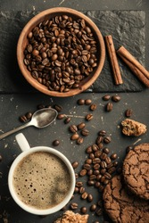 Black fried coffee beans in cafe with cookie and cake on dark textured background