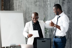 Black friends businessmen rejoice at a new contract with a competitor. People are standing in the office