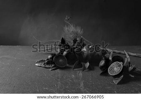 Black fruit composition. Decay still life with black lemons, black oranges, black leaves and black pomegranate on a grunge table. Dark background. Memento moris concept.