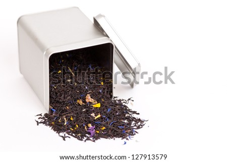 Black fruit tea spilling out of a tea box