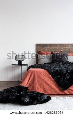 Black furry blankets and pillows on coral bedclothes in white bedroom #1428289016