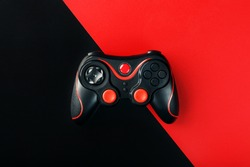 Black gamepad on a black red background, . Gaming concept.