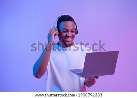Black Gamer Man In Wireless Headset Playing Video Games On Laptop, Looking At Computer Screen While Standing In Vivid Neon Light Over Purple Studio Background, Guy Enjoying Cyber Gaming, Copy Space