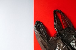 Black garbage bag roll on red and gray background. Ecological concept. Place for the inscription.