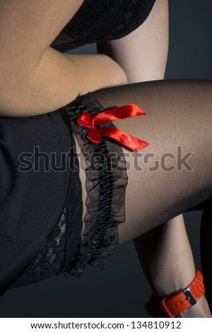 Black garter with red bow on young thigh