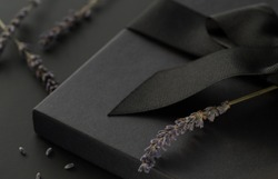 Black gift box on a dark background, decorated with a textured bow and lavender, creating a romantic atmosphere. Typically used for birthday, anniversary presents, gift cards, post cards, letters.