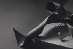 Black gift box with a dark bow and dry branch closeup. Elegant present for birthday, holiday anniversary with dark grey background