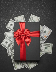 Black gift box with a red ribbon and a big bow on a pile of money. Gift on a granite surface.