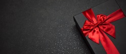 Black gift box with a red ribbon and a large bow on a granite dark background. Place for the inscription