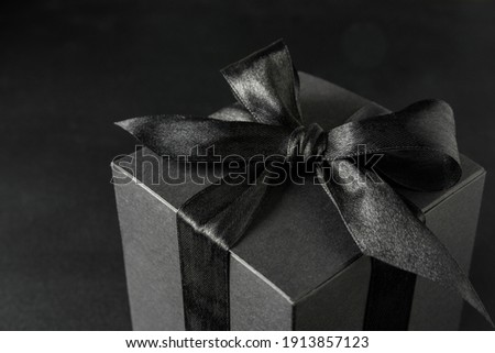 Black gift box with bow on black background, close up Stock photo ©