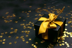 Black gift box with gold ribbon and gold star sequins on a black background. Holiday or black friday concept.