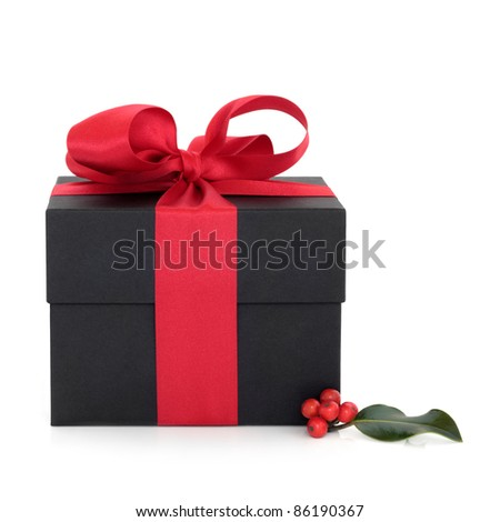 Black gift box with red satin ribbon and bow and christmas holly berry leaf sprig isolated over white background.
