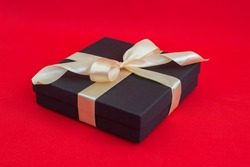 black gift box wrapped with gold ribbon and a bow on red background