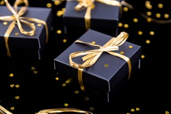 Black gift boxes with gold ribbon on shine background. Close up